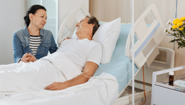 Man receiving IV cancer treatment in hospital with partner at bedside