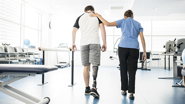 A physical therapist supports a man with a prosthetic leg as he walks
