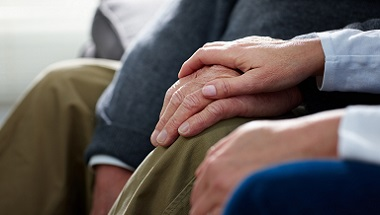 Nurse holding hand of older person