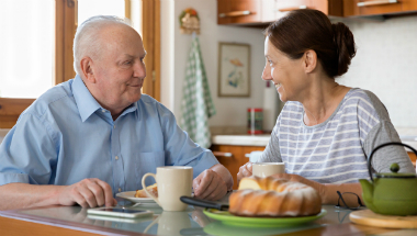 home social care worker eating meal with elderly man
