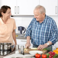Social care staff with elderly man cooking at home