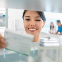 pharmacist taking medicines off shelf